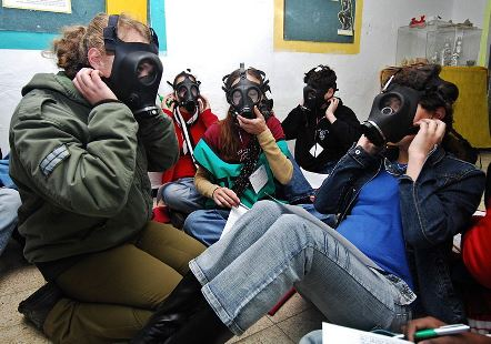 An Israeli soldier practices putting on gas masks with students and their teacher during Israel's annual nationwide home front protection drill in schools.