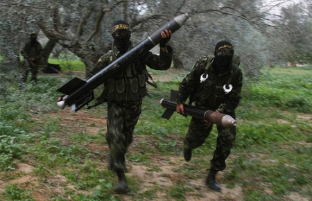 Masked Palestinian militants from Islamic Jihad run with homemade rockets to put in place before later firing them into Israel on the outskirts of Gaza City.